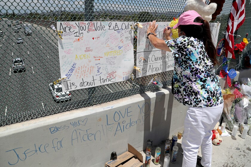 Patricia Alkawadri of Santa Ana leaves a message at a makeshift memorial for 6-year-old Aiden Leos of Costa Mesa.
