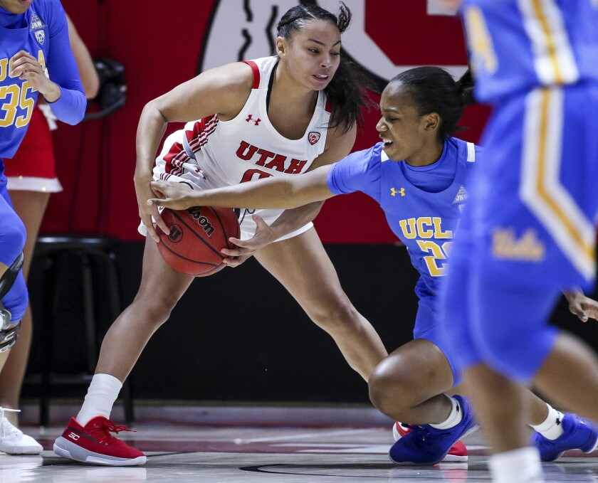Utah guard Kiana Moore (0) grabs the ball as UCLA guard Charisma Osborne (20) moves in to strip it away during an NCAA college basketball game in Salt Lake City, Friday, Jan. 10, 2020. (Spenser Heaps/The Deseret News via AP)