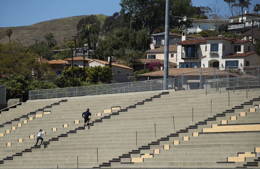People run up the steps while working out at Larrabee Stadium on the Ventura High School campus. The stadium is closed as a result of the coronavirus outbreak but people are climbing over the fence to get inside.
