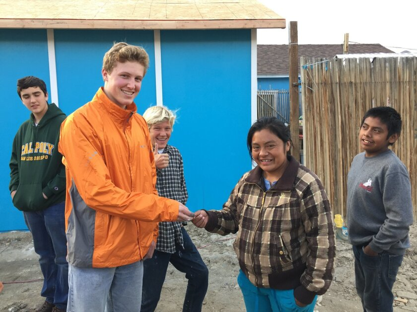 George Champion hands over the key to the new house in Tijuana, while his brother, Arthur, gives the thumbs up.