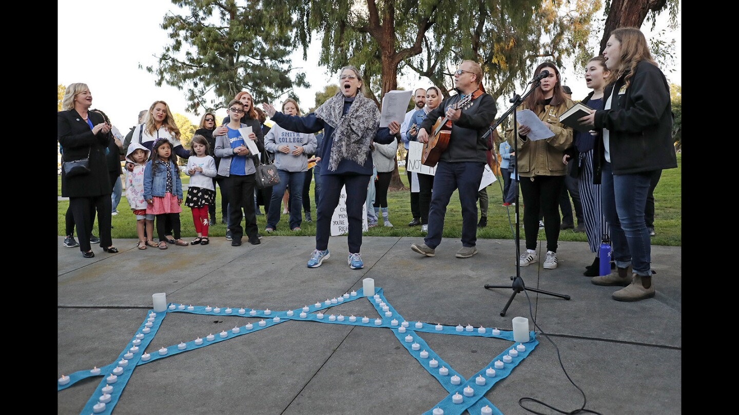 Jewish Collaborative of Orange County founder Rabbi Marcia Tilchin, center, leads a group in song during a shabbat service and vigil as part of a solidarity rally at TeWinkle Park in Costa Mesa on Friday to address anti-semitism in the community and express solidarity. The vigil was in response to community outrage over photos from a weekend party that featured area high school students giving Nazi salutes over a swastika fashioned from cups during a drinking game.