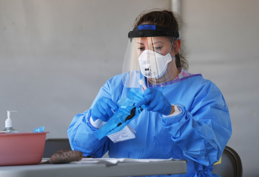 LVN Sarah Johnson prepares a COVID-19 test for a patient at the county's COVID-19 testing site in Mission Valley.