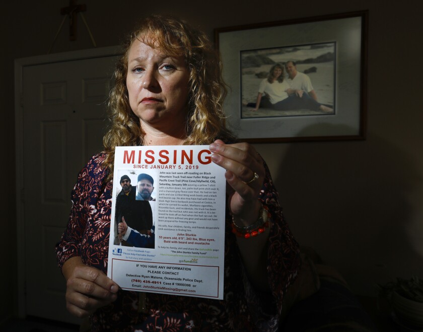 Theresa Sturkie  holds a missing poster at her home on May 21, 2019 in Oceanside, showing her husband of 21 years, John Sturkie, who has been missing since January 5