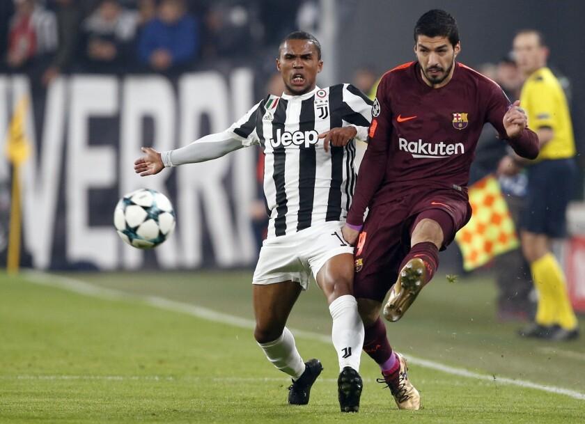 El uruguayo Luis Suárez, del Barcelona, envía un pase junto al brasileño Douglas Costa, de la Juventus, en un encuentro de la Liga de Campeones de Europa disputado el miércoles 22 de noviembre de 2017 en Turín, Italia
