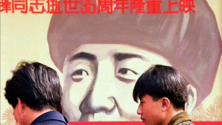 """People wait in 1997 outside a Beijing theater featuring a poster for a movie about Lei Feng, a 1960s soldier who was promoted to hero status by Chinese authorities. The Xinhua News Agency says fast-food chain KFC launched its first """"Lei Feng Spirit"""" restaurant on March 5, 2019."""