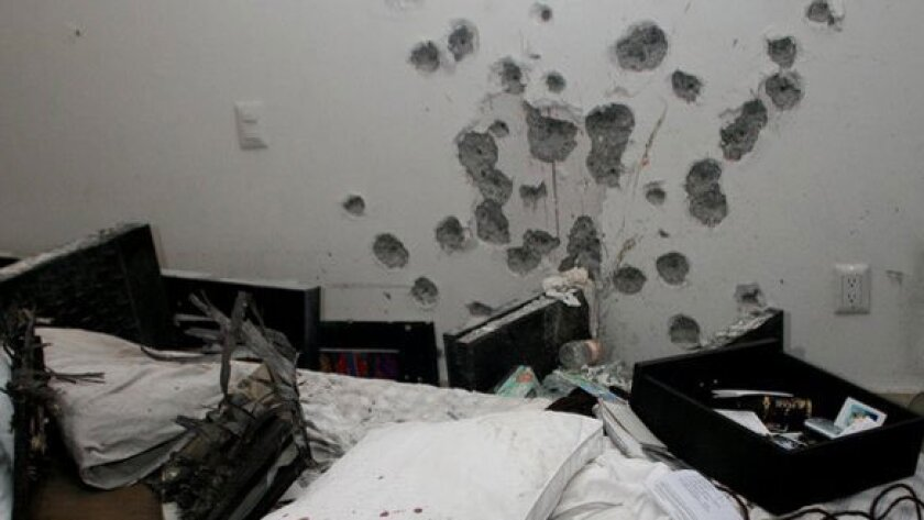 Photographs and other items on a bed next to a bullet-riddled wall in an apartment in Cuernavaca, Mexico after alleged drug cartel chief Arturo Beltran-Leyva and three members of his cartel were killed during a shootout with Mexican Navy Special Forces.