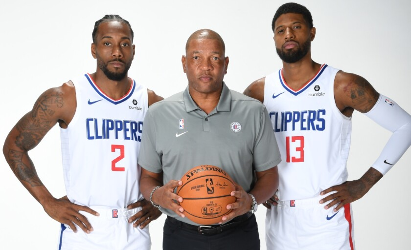 Doc Rivers with his star players Kawhi Leonard (2) and Paul George (13) for a photo shoot during media day.