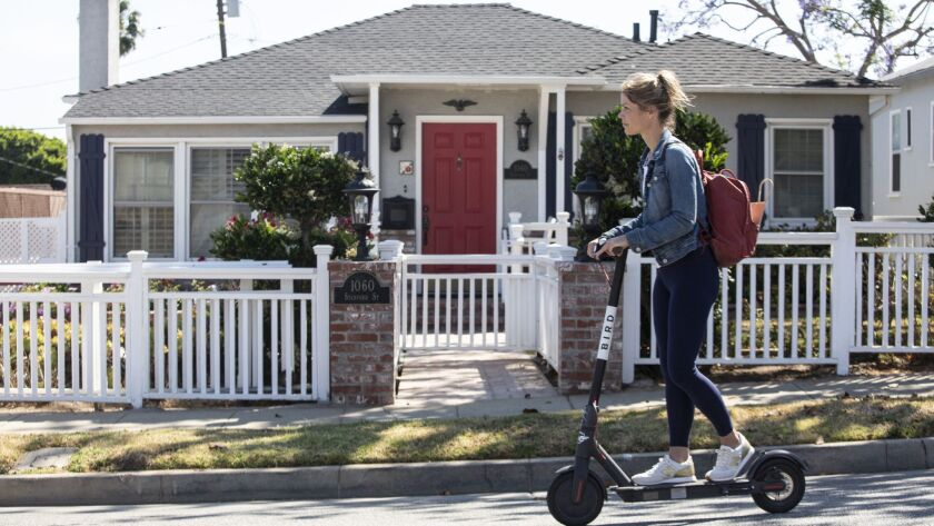 A woman rides a scooter down Stanford Street in Santa Monica where several homes were inherited.