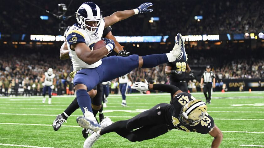 NEW ORLEANS, LOUISIANA, NOVEMBER 4, 2018-Rams running back Malcolm Brown leaps over Saints safety Ma