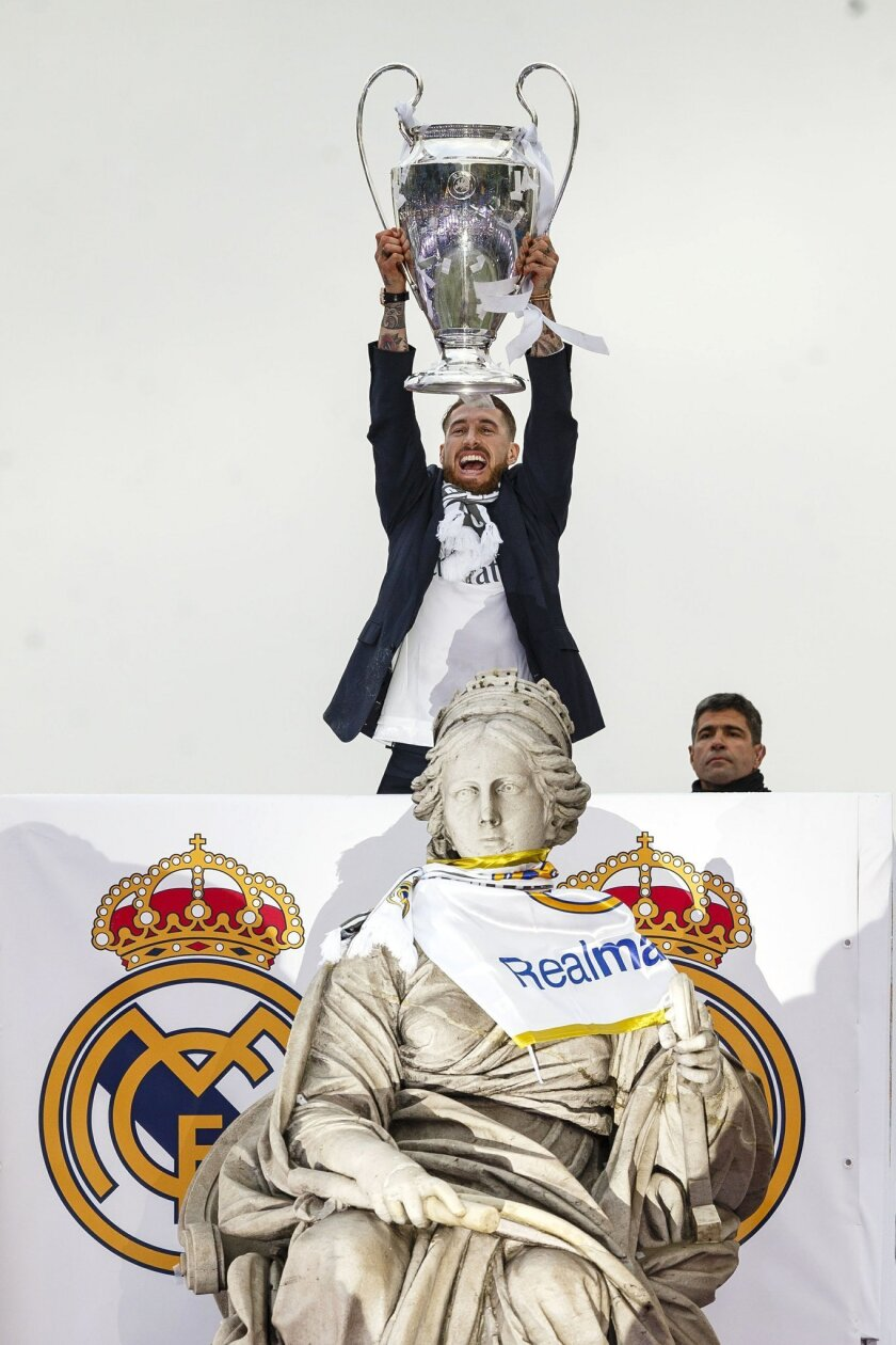 Real Madrid player Sergio Ramos holds the trophy at Cibeles square after winning the Champions League final soccer match between Real Madrid and Atletico Madrid, during a celebration parade in Madrid, Sunday, May 29, 2016. Real Madrid won 5-3 on penalties after the match ended 1-1 after extra time.