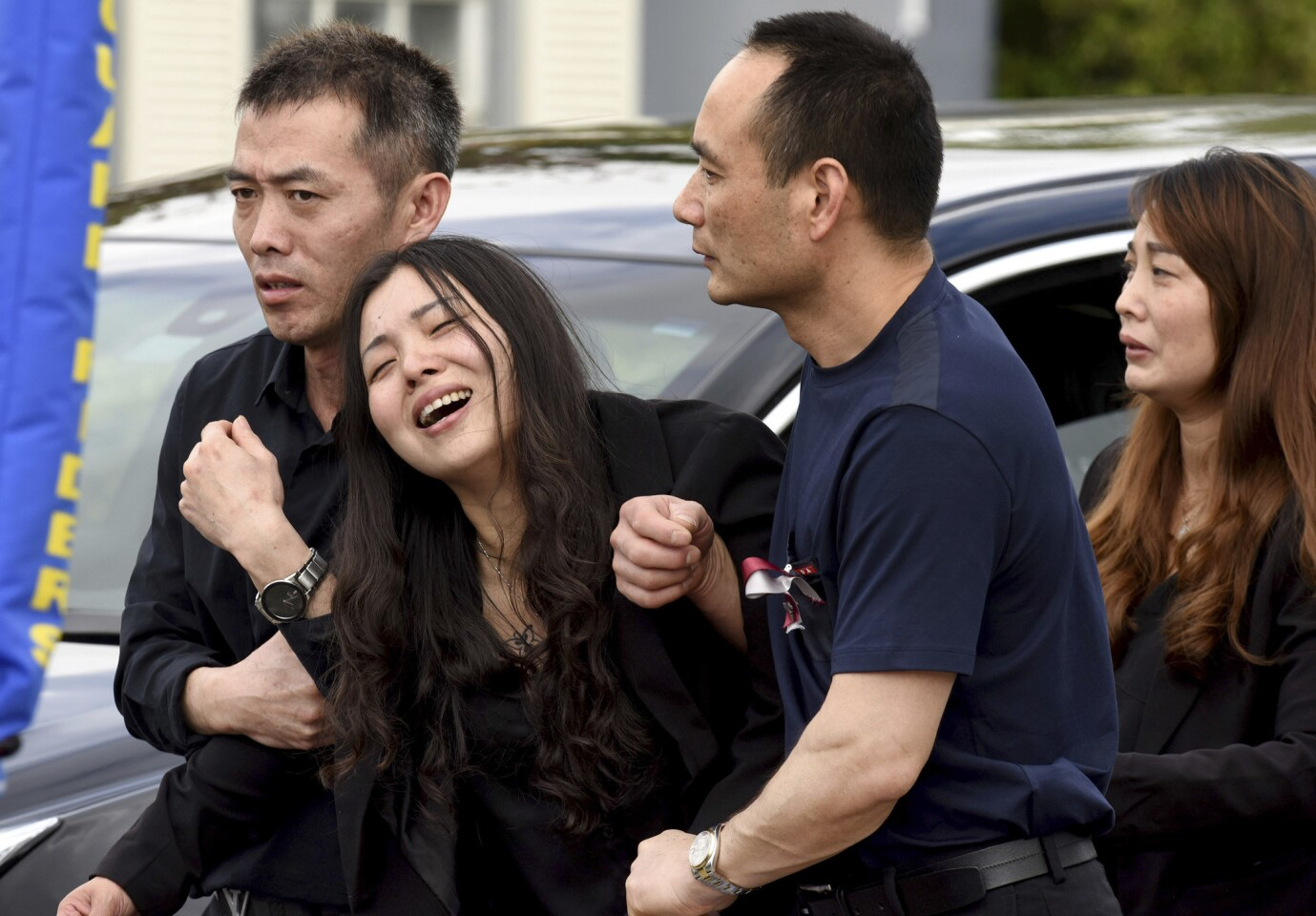 Peter Wang's mother, Hui, cries as she is helped into a waiting car with her family after the memorial service for her 15-year-old son in Coral Springs, Fla., on Feb. 20, 2018.