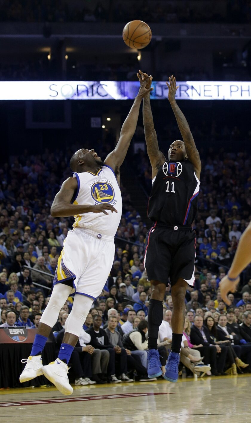 Los Angeles Clippers' Jamal Crawford (11) shoots over Golden State Warriors' Draymond Green (23) during the first half of an NBA basketball game Wednesday, March 23, 2016, in Oakland, Calif. (AP Photo/Marcio Jose Sanchez)