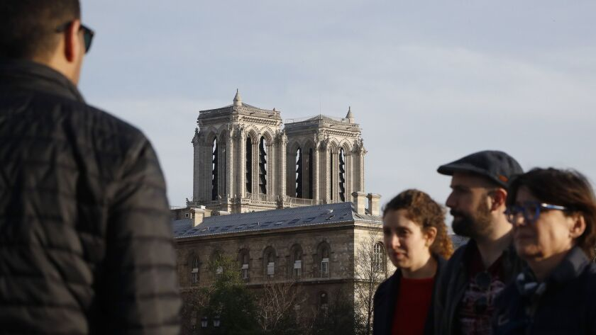 A man looks at the Notre Dame Cathedral from the Change bridge in Paris, Wednesday, April 17, 2019.