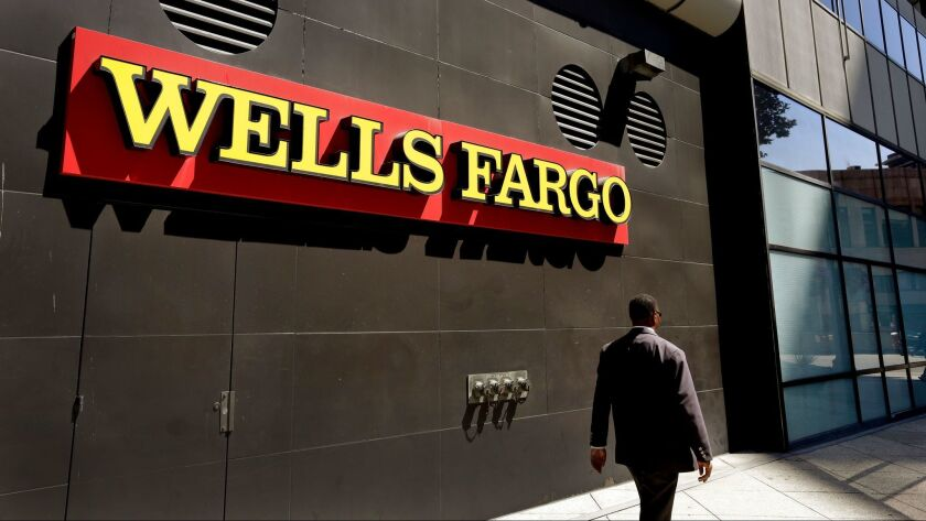 FILE - In this July 14, 2014 file photo, a man passes by a Wells Fargo bank office in Oakland, Calif