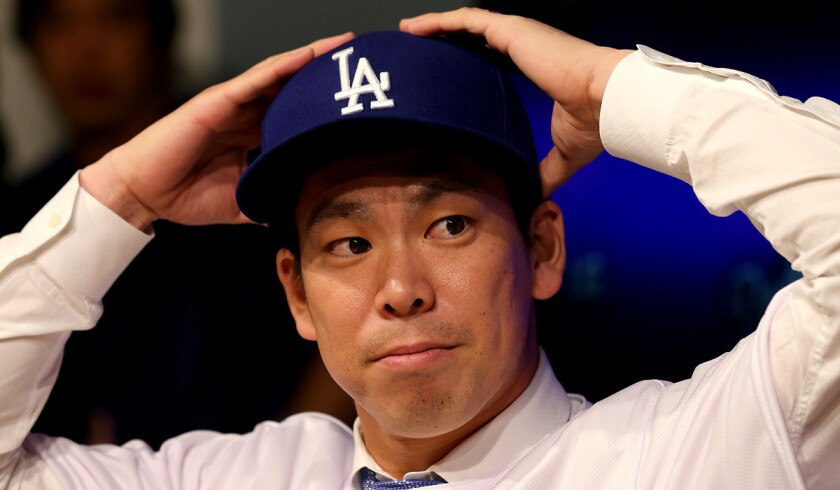 Pitcher Kenta Maeda, the Dodgers most recent acquisition, tries on a Dodgers cap and jersey during a press conference at Dodger Stadium on Thursday.