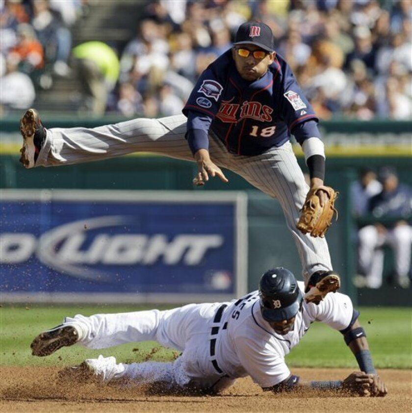 Minnesota Twins shortstop Orlando Cabrera, top, jumps to avoid Detroit Tigers Marcus Thames while trying to turn a double play in the fourth inning of a baseball game in Detroit, Thursday , Oct. 1, 2009. The Tigers' Brandon Inge was safe at first base on the play. (AP Photo/Paul Sancya)