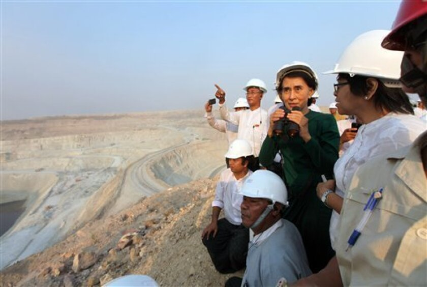 Myanmar's opposition leader Aung San Suu Kyi uses binoculars to look at the Letpadaung copper mine project during a visit to Myanmar Yang Tse Copper Limited in Monywa, 760 kilometers (450 miles) north of Yangon, central Myanmar, Thursday, March 14, 2013. In talks with villagers, Suu Kyi failed to persuade her listeners to agree with the conclusions of an official panel she headed that the national interest was best served by allowing continued operation of the Letpadaung copper mine, to encourag