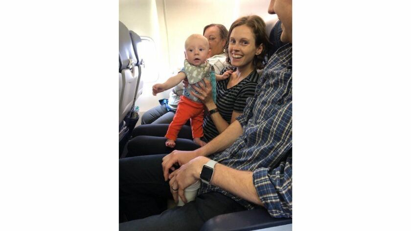 Samantha Kellgren of Chicago holds her baby, Owen, on a recent flight to Boston. Kellgren and her husband weren't sure how their infant son would be on his first flight, so they brought goody bags with ear plugs, snacks and other treats for fellow passengers.