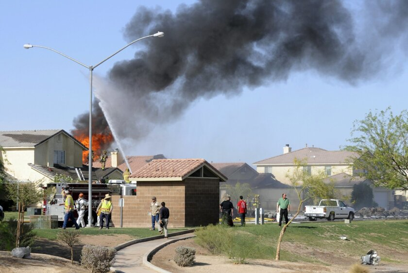 Smoke and flames rise after a Marine jet crashed into a residential area in the desert community of Imperial, Calif., setting homes on fire Wednesday, June 4, 2014. The pilot ejected safely. The Harrier AV-8B went down in Imperial, about 90 miles east of San Diego. (AP Photo/Imperial Valley Press,