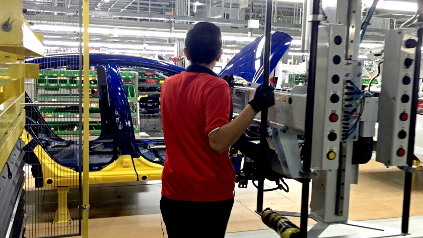 A worker assembles the Forte sedan on the floor of a Kia plant in Nuevo Leon, Mexico.