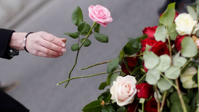 A woman places a flower Saturday following an attack in central Stockholm.