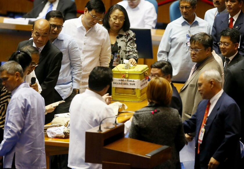 Philippine House and Senate election tribunal staff examine the contents of the ballot boxes from Davao Del Sur province in southern Philippines as the official count of votes cast in the May 9 presidential election begins Wednesday, May 25, 2016 in the Lower House in suburban Quezon city, northeast of Manila, Philippines. The Philippine Congress on Wednesday started the official count, though confirmation of Rodrigo Duterte's apparent victory may be slowed by disputes in the more closely fought vice presidential race. (AP Photo/Bullit Marquez)
