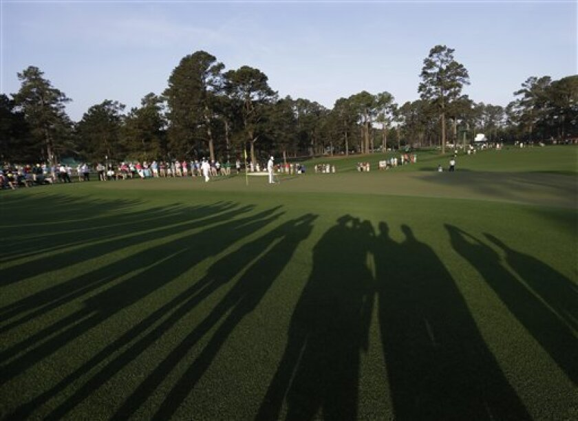 Bubba Watson and Scott Piercy putt on the second green during a practice round for the Masters golf tournament Tuesday, April 9, 2013, in Augusta, Ga. (AP Photo/Darron Cummings)
