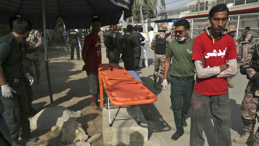 Volunteers wait outside the Chinese Consulate after an attack in Karachi, Pakistan, Friday, Nov. 23,