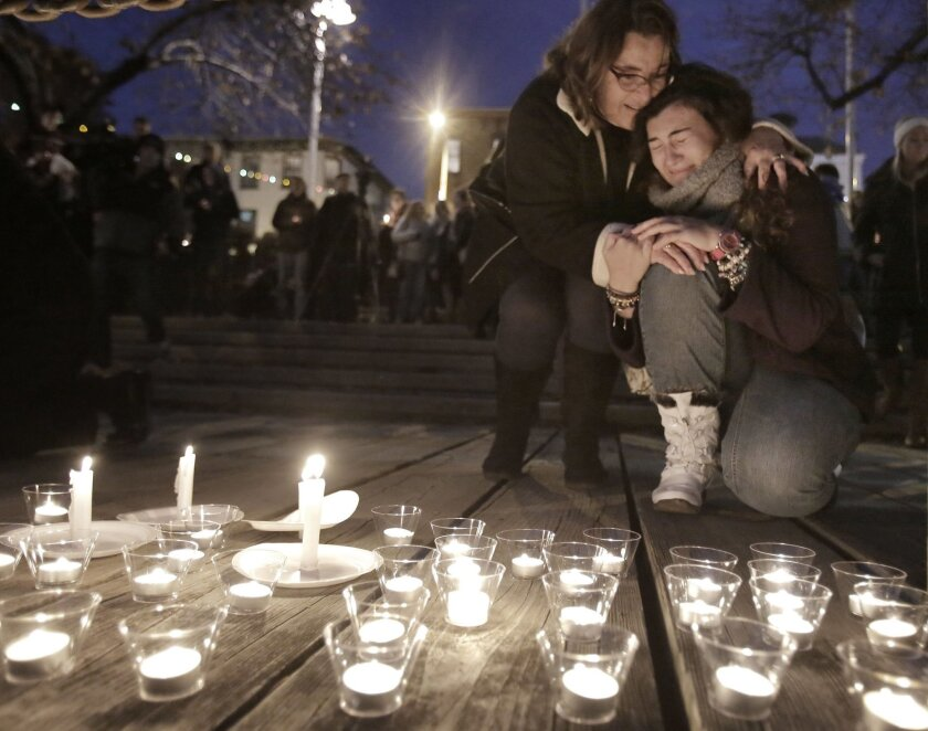 After leaving a candle at the edge of the Manayunk Canal, a woman is comforted by another during a candlelight vigil, for Shane Montgomery, at a park across from Kildare's Irish Pub in the Manayunk section of Philadelphia, Pa., Saturday, Nov. 29, 2014. Montgomery, who is still unaccounted for, was last seen leaving Kildare's Pub early Thanksgiving morning. (AP Photo/The Philadelphia Inquirer, Elizabeth Robertson)