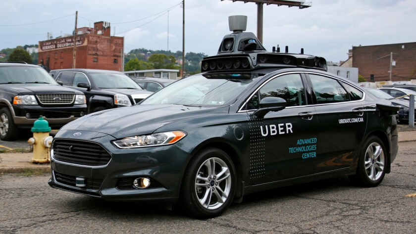 A self-driving Uber car makes its way down River Road in Pittsburgh.