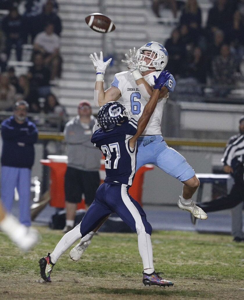 Corona del Mar High wide receiver John Humphreys jumps over Camarillo's Izaiah Lazaro to make a catch in the second quarter of the CIF Southern Section Division 4 semifinal playoff road game on Nov. 16, 2018.