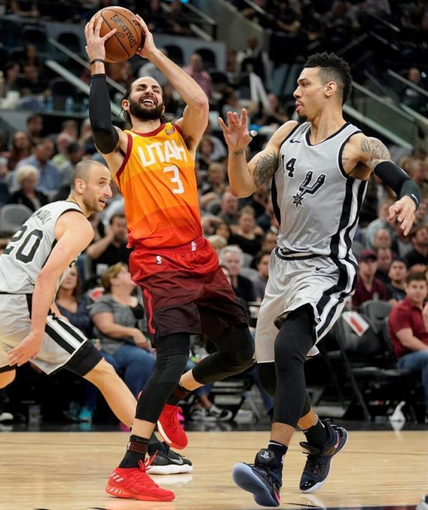 El base español de los Jazz de Utah Ricky Rubio con el balón ante los jugadores de San Antonio Spurs Danny Green (d) y Manu Ginobili, durante el partido de liga regular de la NBA disputado en el AT&T Center de San Antonio. EFE