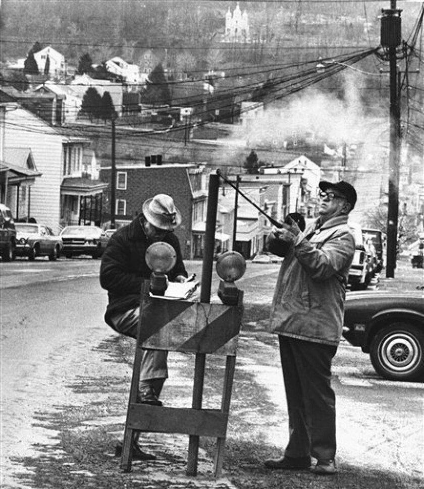 """FILE - In this April 1981 file photo, U.S. Bureau of Mines' John Stockalis, right, and Dan Lewis drop a thermometer through a hole on Main Street in Centralia, Pa., to measure the heat from a shaft mine blaze that burns under the town. The few remaining residents of the Pennsylvania coal town decimated by a 48-year-old underground mine fire claim in court papers that a """"massive fraud"""" is being perpetrated against Centralia by parties seeking to grab the mineral rights to hundreds of millions of dollars worth of coal. (AP Photo/Paul Vathis, File)"""