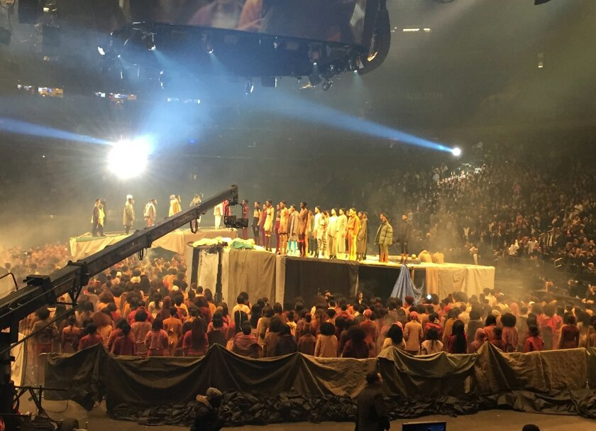 """Models stand on stage as  Kanye West presents his Yeezy collection at Madison Square Garden during Fashion Week, Thursday, Feb. 11, 2016, in New York. West played songs from his latest album, """"The Life of Pablo,"""" out on Friday. (AP Photo/Leanne Italie)"""
