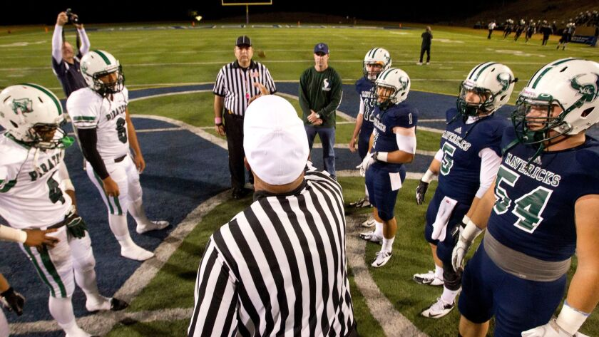 Oceanside and La Costa Canyon players watch as the referee flips the coin at La Costa Canyon High School on Friday.