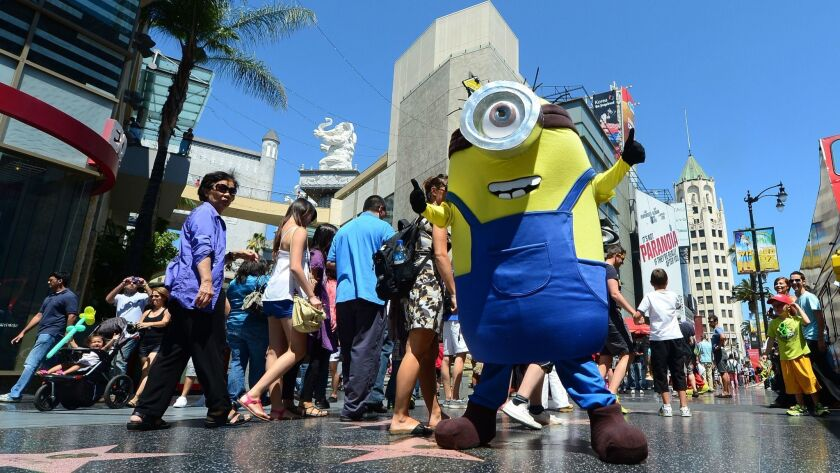 A man dressed in a Minion costume from the 'Despicable Me' movies strikes a pose along Hollywood Boulevard in L.A. The county set a record for hosting tourists for the seventh year in a row.