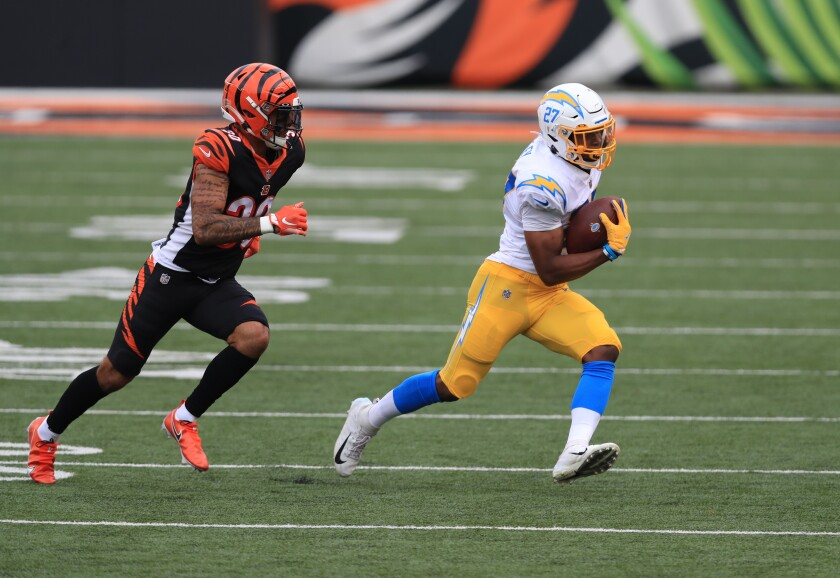Chargers running back Josh Kelley is chased by Cincinnati Bengals' Jessie Bates.