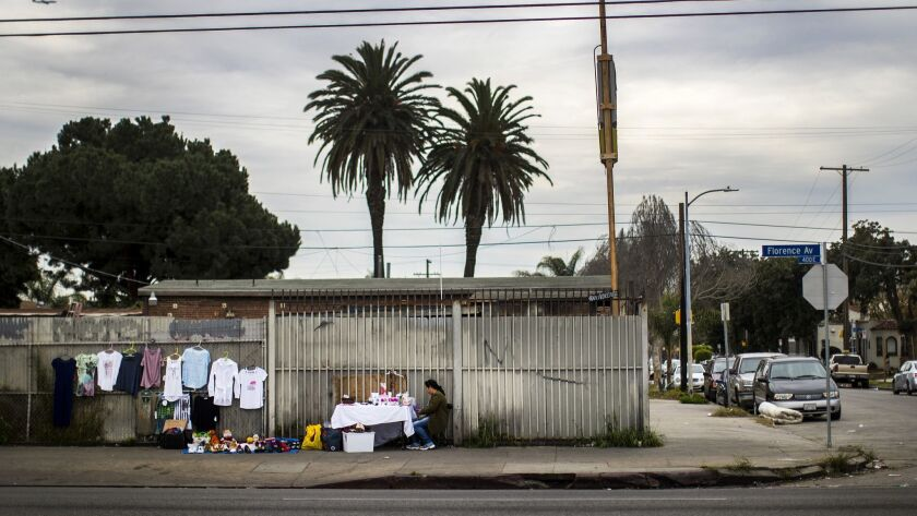 LOS ANGELES, CA - MARCH 7, 2018: A woman sells her wares in front of a fenced in lot in the 400 bloc