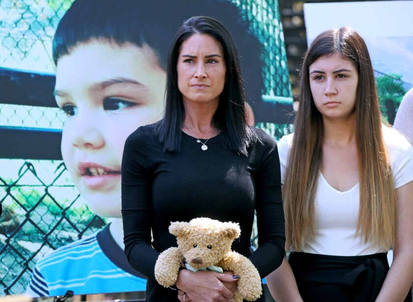 Two people, one holding a teddy bear, stand before a large photo of a child.