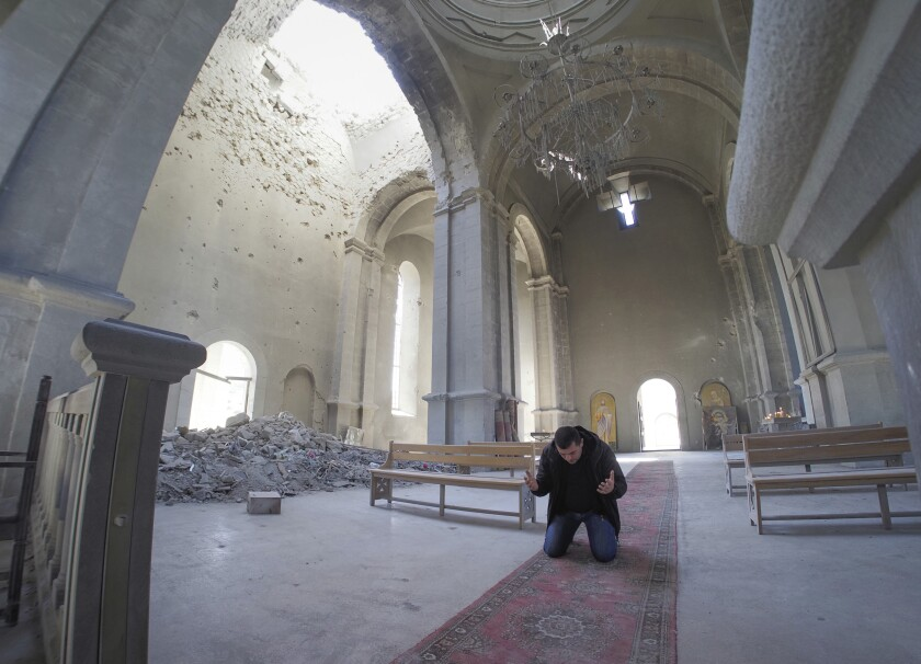 Un hombre reza en una catedral dañada por bombardeos en Shushi, en las afueras de Stepanakert
