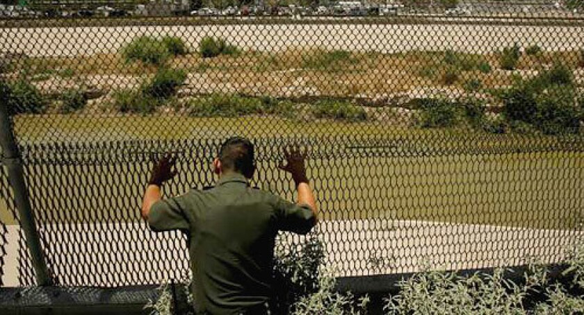 A U.S. Border Patrol agent scans the Rio Grande through a fence after seeing four people attempt to cross the US-Mexico border illegally.