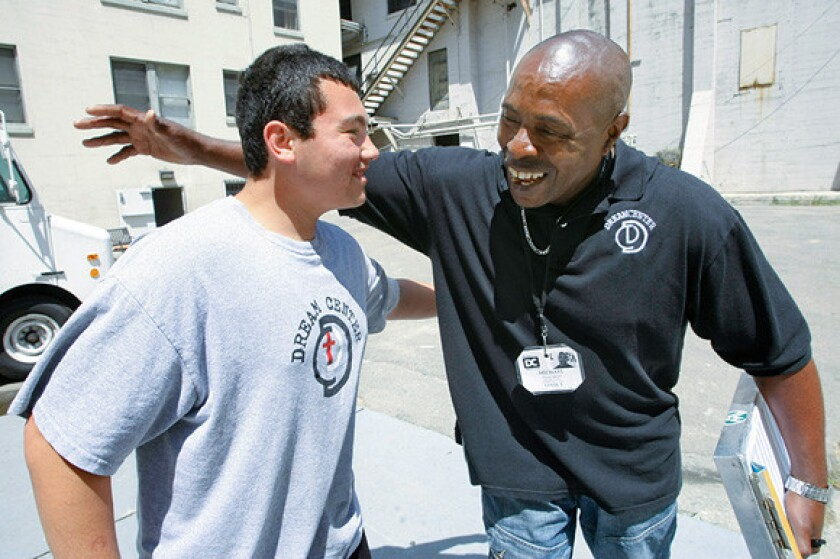 Michael Banyard, right, who is in the men's discipleship program at the Dream Center in Echo Park, hugs Jose Monrial, 15. As a crew leader at the Dream Center's construction department, Banyard taught Jose about drywall and paint.