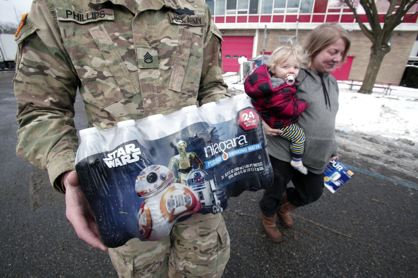 A Michigan National Guardsman helps Flint resident Amanda Roark and her son Dash unload bottled water distributed at a Flint fire station.