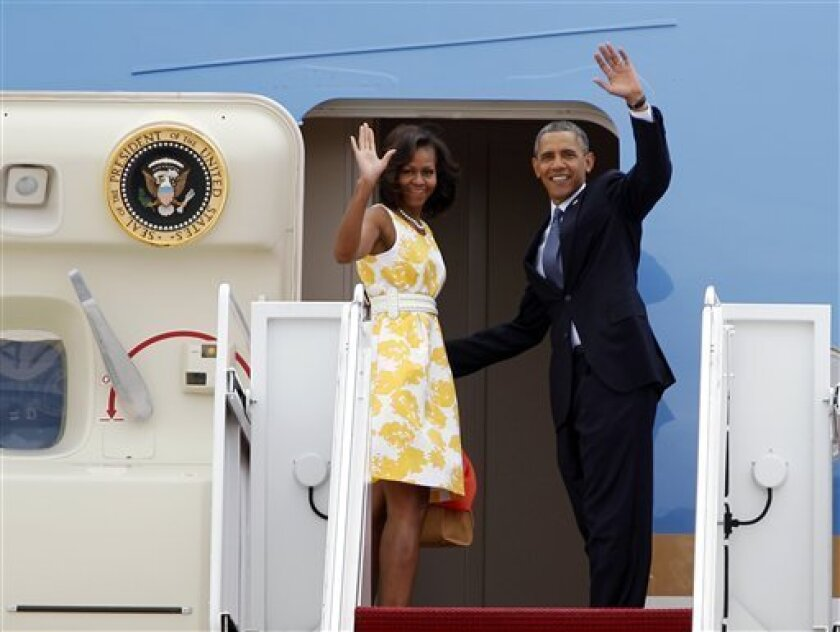 President Barack Obama and first lady Michelle Obama wave as they board Air Force One before departing Andrews Air Force Base, Md., Saturday, Aug. 10, 2013. The President and first lady are traveling to Orlando, Florida, where they will address injured veterans at the Disabled American Veterans National Convention, then follow on to their vacation at Martha's Vineyard. (AP Photo/Jose Luis Magana)