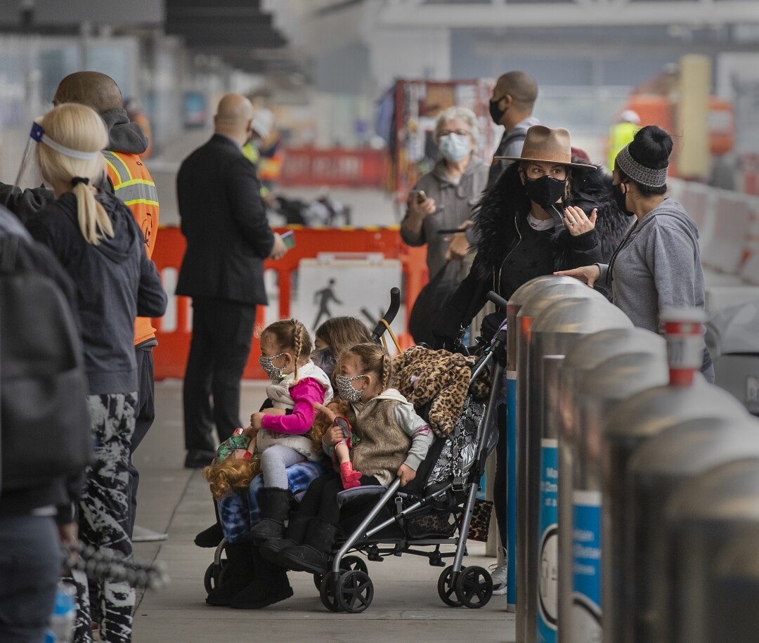 Travelers wearing face coverings arrive at Los Angeles International Airport.