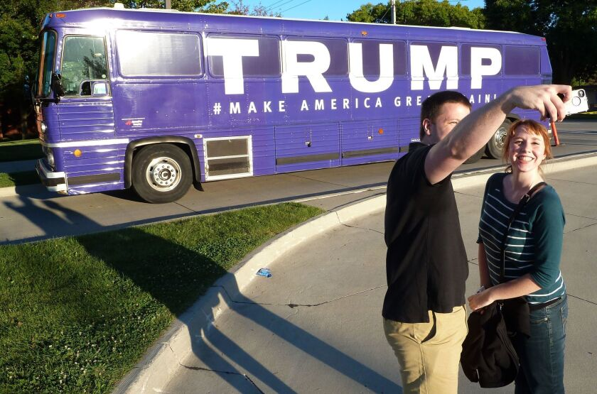 People take a photo in front of a Donald Trump's campaign bus in Urbandale, Iowa, on September 19, 2015, when it was still his campaign bus.