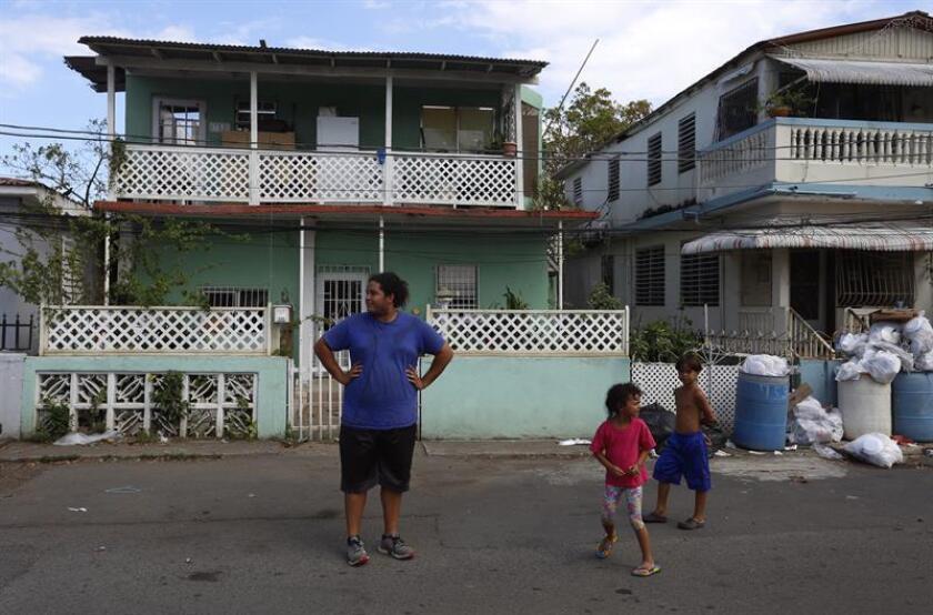 Un joven y dos niños caminan frente a casas destrozadas por el paso del huracán María en el Barrio Obrero del distrito de Santurce, en San Juan (Puerto Rico). EFE/Archivo