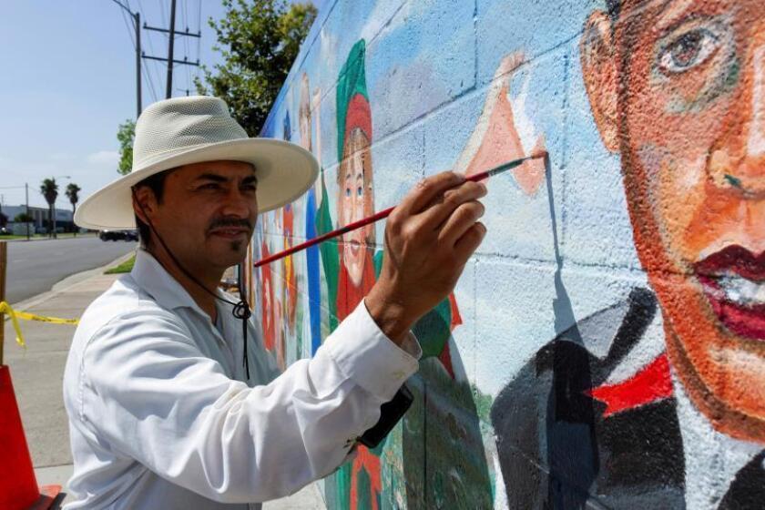 """El artista Emigdio """"Higgy"""" Vásquez trabaja el pasado 29 de agosto en la restauración del mural """"Los Niños del Mundo"""", pintado en 1994 por su padre Emigdio Vásquez (1939-2014) en un pared del parque Lemon en la ciudad de Fullerton, California. EFE/Felipe Chacón"""