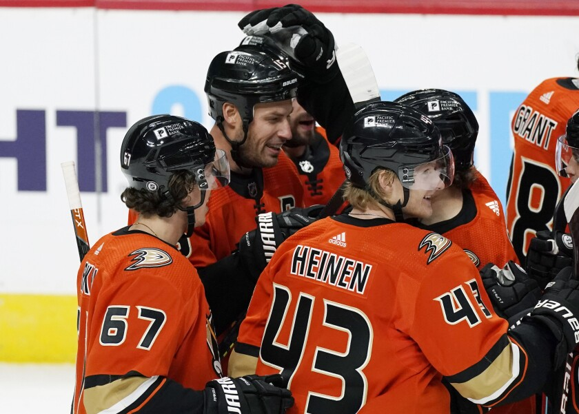 The Ducks' Ryan Getzlaf, back left, is congratulated on his overtime goal at Colorado by Sam Steel, back right.