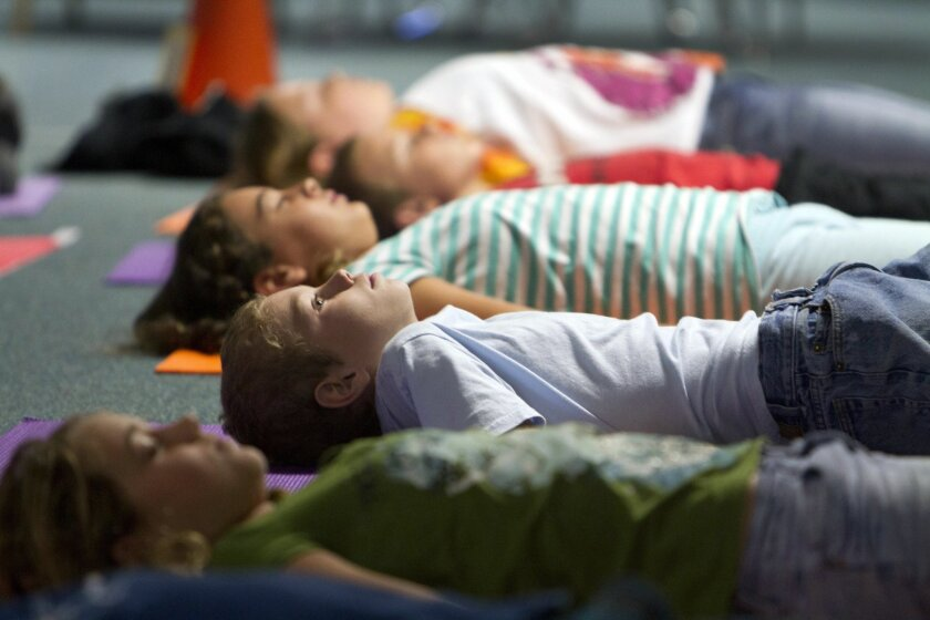 In this photo from 2012, fifth grade students finish a yoga class by quietly lying on their mats at Flora Vista Elementary School in Encinitas.